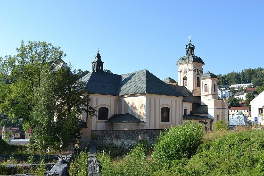 Pohľad na kostol Nanebovzatia Panny Mária od zadnej strany, v popredí ruiny zaniknutého kláštora